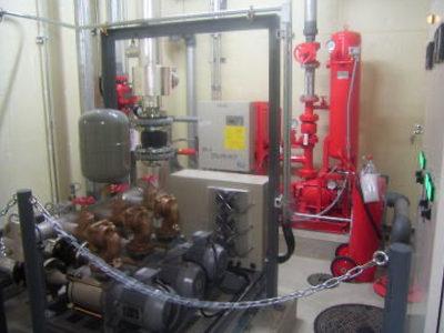 1階ポンプ室 スプリンクラーポンプ(奥の赤色)、給水加圧ポンプユニット(手前)を設置し、万一の時の火災の備えとしています。  *スプリンクラー設備とは火災が発生した場合、天井部に設置したスプリンクラーヘッドが、自動的に火災を感知し、自動的に放水され、消火する設備です。