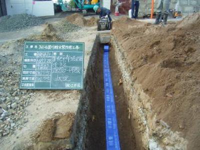 屋外給水工事。配管完了後、埋め戻ししている状況です、青いテープは、埋設シートと言って「この下に水道管が埋まっている」と表示しています。<br /> 他の人がここを掘った時水道管を傷つけないようにする為に設置します。