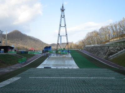 麓に高さ30m、頂上に高さ25mの鉄塔を建てて、その間にワイヤーを張り、ロープウェイのように頂上まで資機材を運びました。